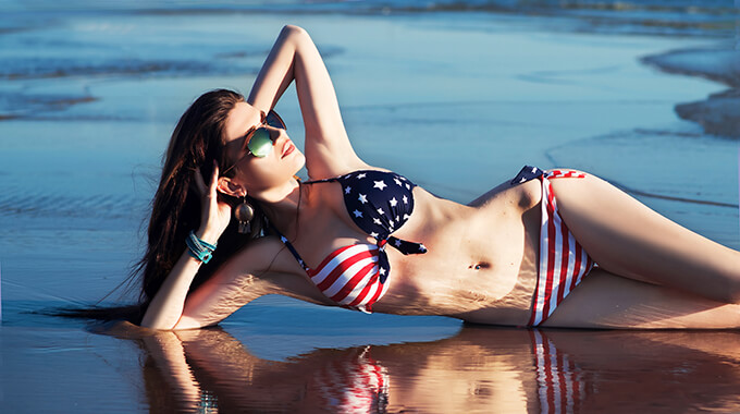 Woman on beach wearing USA flag swimsuit
